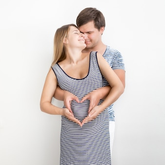 심장의 모양에 손을 잡고 행복 한 포옹 임신 부부의 초상화