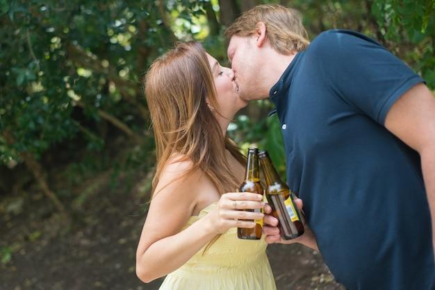 幸せな夫と妻のキスの肖像画。ビール瓶を持って、愛情を示す中年の成人男性と女性