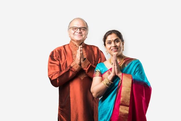 白い背景の上に分離された伝統的な服装で幸せなインドのアジアのシニアまたは引退したカップルの肖像画