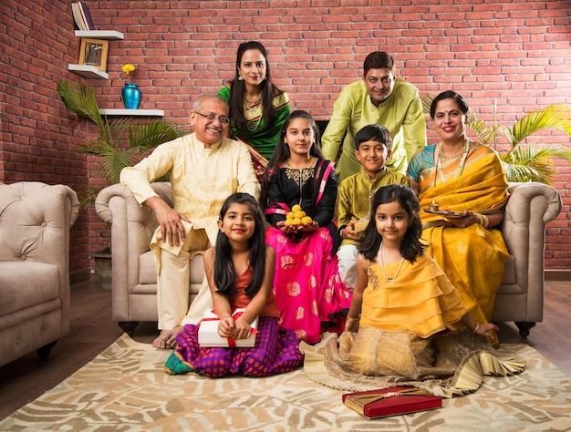 Портрет счастливой индийской семьи в традиционной одежде, сидя на диване в помещении