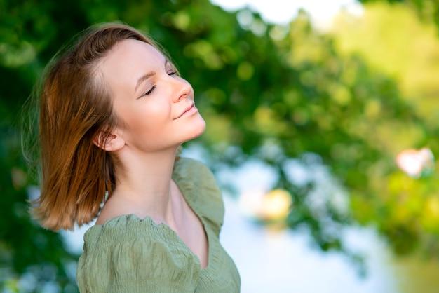 행복하고 즐거운 아름다운 소녀의 초상화, 편안하고 차분한 젊은 여성이 여름 햇살 가득한 공원에서 걷고 있고, 좋은 날씨를 즐기고, 깊고 신선한 공기를 마시고, 웃고 있습니다. 복사 공간, 자연 배경