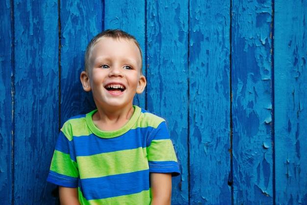 Портрет счастливого радостного красивого маленького мальчика на фоне старой текстурированной синей стены