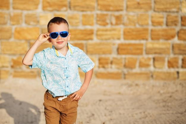 Портрет счастливого радостного красивого мальчика перед желтой кирпичной стеной.