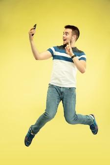 Портрет счастливого прыгающего человека с гаджетами на желтой стене