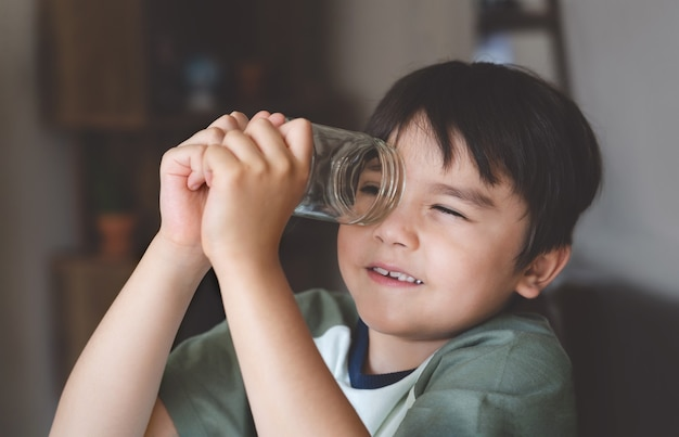 유리 항아리를 통해 찾고 행복 한 아이의 초상화입니다. 집에서 놀고 배우기, 탐색 개념