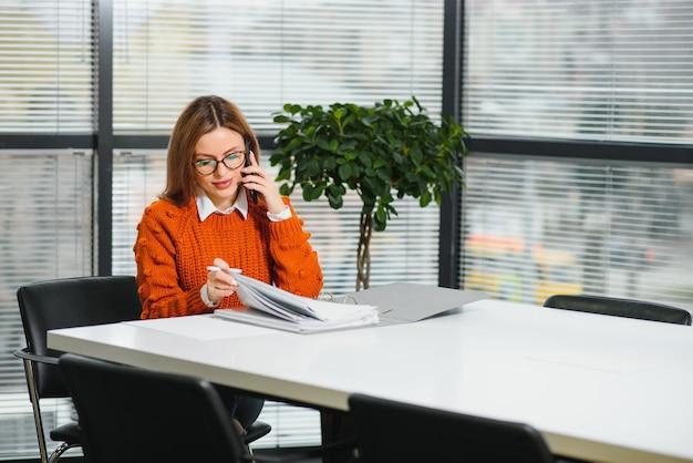 Портрет счастливой леди, печатающей в мобильном телефоне, находясь за столом в офисе