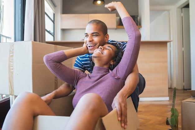Портрет счастливой латинской пары, весело проводящей время с картонными коробками в новом доме в день переезда. понятие недвижимости.