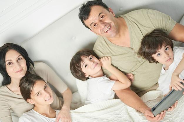 행복한 라틴 가족의 초상화, 어린 아이들과 부모가 함께 시간을 보내고 아침에 침대에 머물면서 카메라를 보며 웃고 있습니다. 부모, 어린이 개념