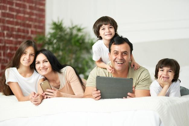 디지털 기기를 사용하는 동안 카메라를 보고 웃고 있는 귀여운 아이들과 함께 침대에 누워 있는 행복한 라틴 가족의 초상화. 가족, 부모, 기술 개념