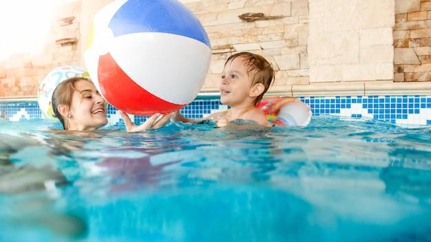 여름 호텔 리조트 수영장에서 다채로운 풍선 비치 볼을 가지고 노는 젊은 어머니와 함께 행복 웃음 유아 소년의 초상화