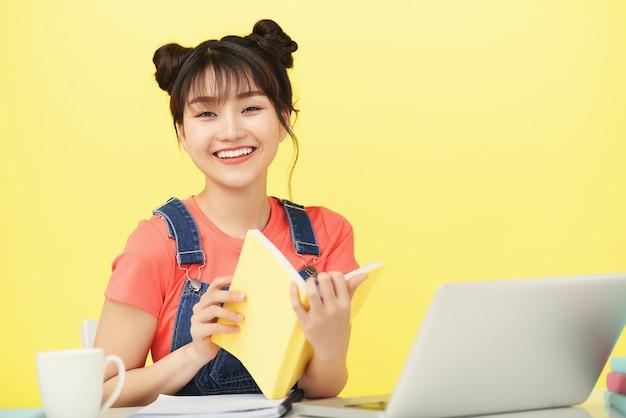 本を読んで、クラスの資料を改訂する幸せな笑いの若い大学生の肖像画