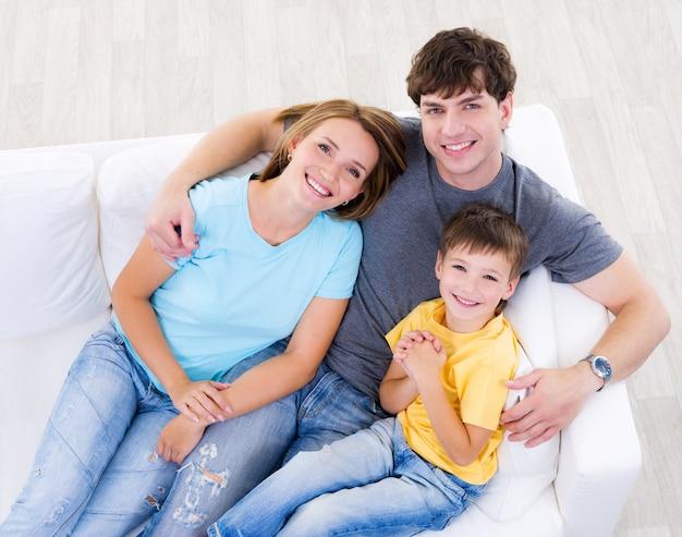自宅のソファでカジュアルに息子と幸せな笑いの若い家族の肖像画-ハイアングル