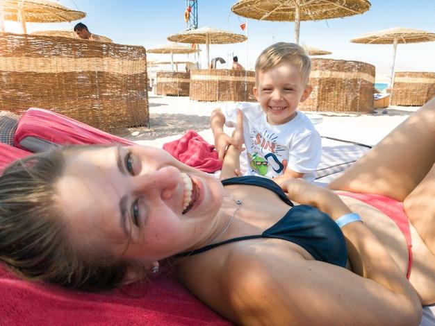 바다 해변에서 일광욕 침대에 누워 그녀의 작은 아들과 함께 행복 한 웃음 젊은 여자의 초상화. 가족 휴식과 여름 휴가 휴가 동안 해변에서 좋은 시간을 보내고