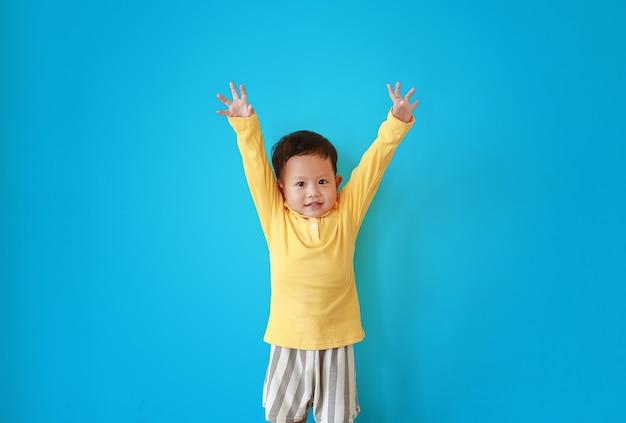 幸せな小さなアジアの男の子の表情の肖像画は、手を上げて、青い背景の上に分離されたカメラを探しています。
