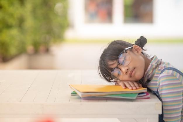 本で眠っている幸せな小さなアジアの子供の肖像画