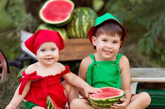 幸せな男の子と女の子の屋外、スイカを食べたり収穫したりする子供の肖像画