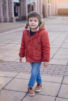 복고 톤 도시 공원에 서 행복 한 어린 소년의 초상화, 활성 자식 쇼핑몰 외부에 서있는 동안 얼굴을 미소와 함께 카메라를 찾고.