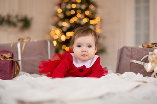 クリスマスツリーの近くにクリスマスプレゼントボックスと赤いニットセーターで幸せな少女の肖像画
