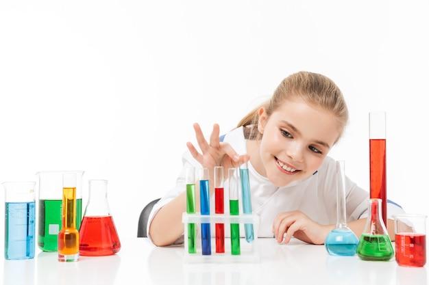 흰색 실험실 코트를 입은 행복한 어린 소녀의 초상화는 흰색 벽에 격리된 테스트 튜브에서 여러 가지 빛깔의 액체로 화학 실험을 하고 있습니다.