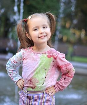 都市公園の噴水近くの幸せな少女の肖像画。