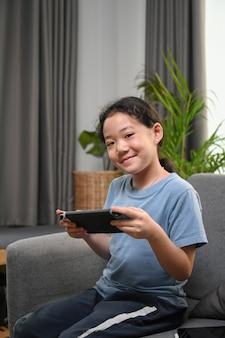 Портрет счастливой маленькой девочки, играющей в видеоигры, сидя на диване у себя дома