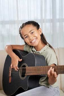 Портрет счастливой маленькой девочки, улыбающейся в камеру, сидя на диване и учится играть на гитаре