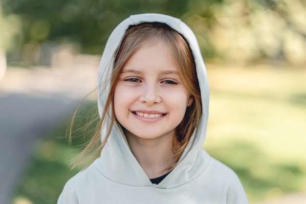 ぼやけた自然の公園を歩きながらカメラに微笑んで幸せな少女の肖像画