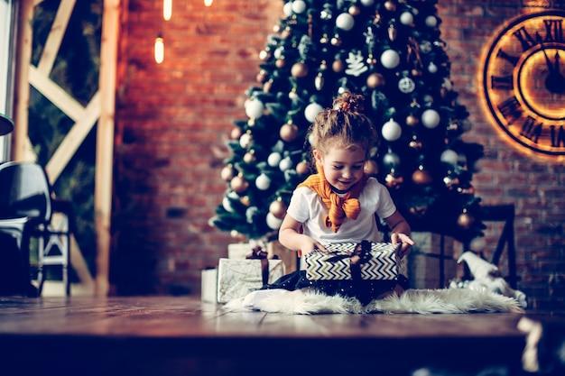 Портрет счастливой маленькой девочки с рождественскими подарками. концепция рождества