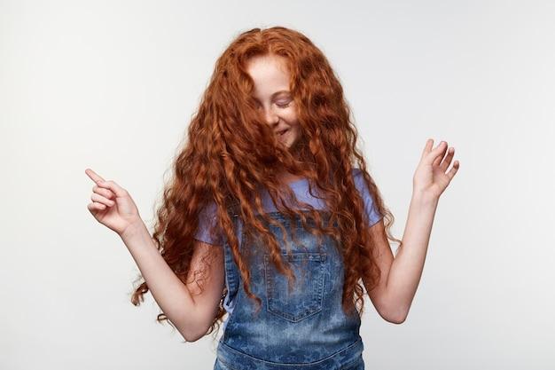 Портрет счастливой маленькой девочки с рыжими волосами и веснушками, слушая любимую песню и танцы, весело проводя время, широко улыбаясь, стоя над белой стеной. Бесплатные Фотографии