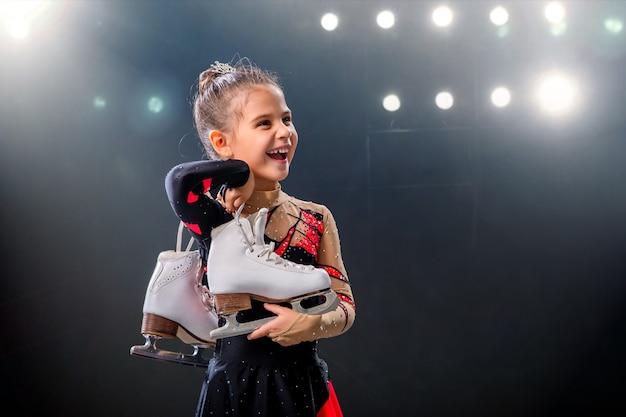 Портрет счастливой маленькой фигуристки с коньками в руках на ледовой арене, темный фон