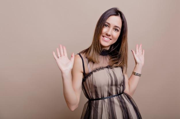 孤立した壁にポーズをとって魅力的な笑顔と幸せな素敵な女性の肖像画は、手を上げて笑顔、幸せな本当の感情、テキストの場所