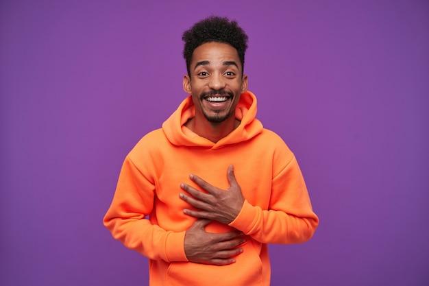 幸せな素敵な若い巻き毛の暗い肌のブルネットの男性の肖像画は、彼の胸に上げられた手のひらを維持しながら、良いニュースを喜んで、紫で隔離されて喜んで笑っています