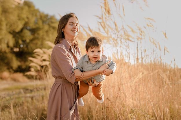 Портрет счастливой любящей матери, обнимающей ее маленького сына в солнечном парке у реки.