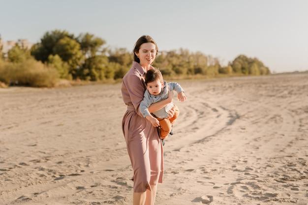川の近くの日当たりの良い公園で彼女の赤ん坊の息子を抱き締める幸せな愛情のある母親の肖像画。