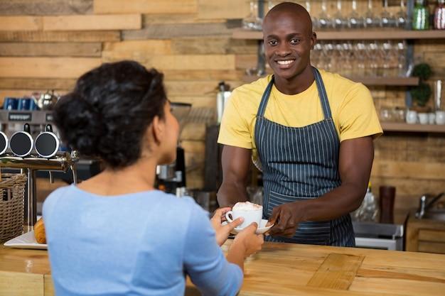 コーヒーショップで顧客にコーヒーを提供する幸せな男性バリスタの肖像画