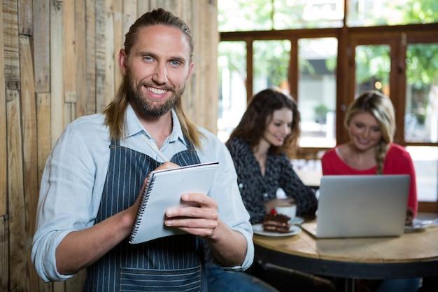 Портрет счастливого мужчины-бариста, пишущего заказы с клиентками на заднем плане в кафе