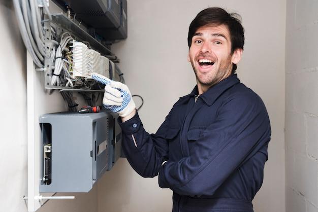 Портрет счастливого мужского электрика указывая на монтажную плату