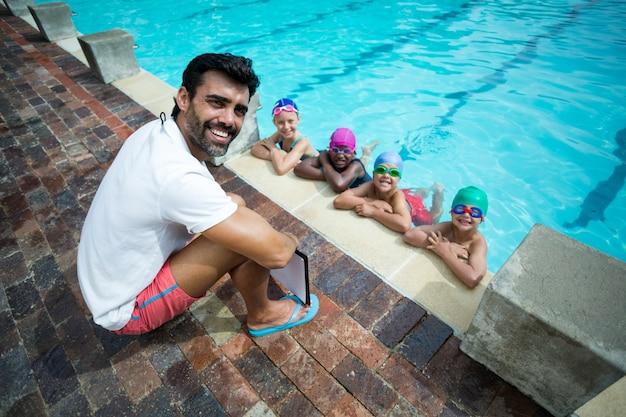 プールサイドで小さな水泳選手と幸せな男性トレーナーの肖像画
