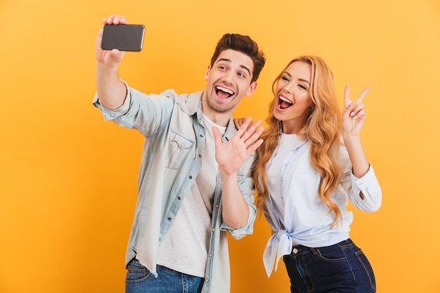 Портрет счастливого мужчины и женщины, делающих селфи фото на мобильный телефон во время жестов