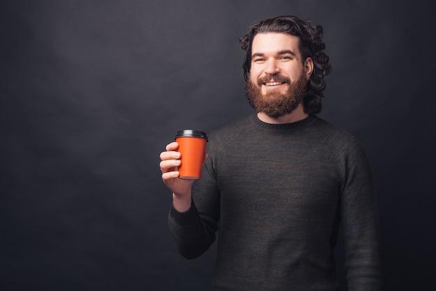 Портрет счастливого человека, держащего красную чашку кофе, чтобы пройти через черную стену