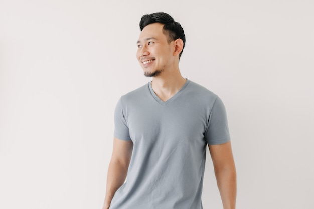 白い背景で隔離の青いtシャツの幸せな男の肖像画