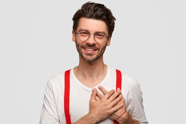 幸せな男の肖像画は、両方の手のひらを心に留め、大きな感謝の気持ちを込めて、スタイリッシュな服を着て、フレンドリーな笑顔を持ち、白い壁に隔離されています。人、感情、積極性