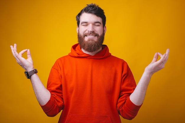 Портрет счастливого человека, размышляя над желтой стеной