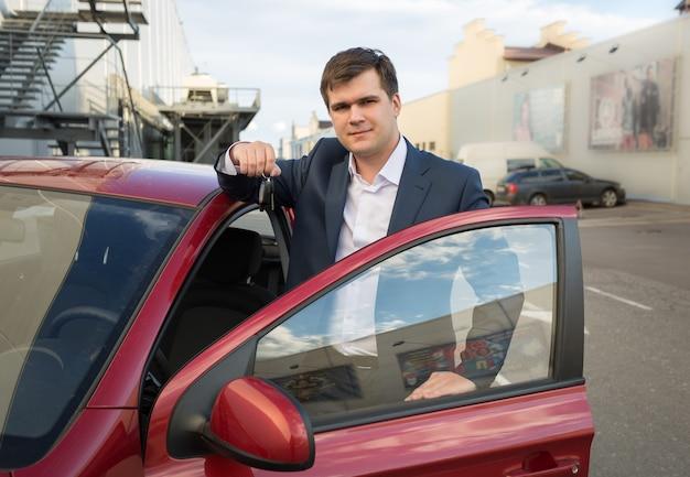 新しい車でポーズをとって鍵を見せて幸せな男の肖像画