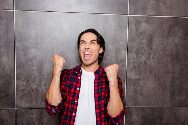 Портрет счастливого человека поднимает руки и успешного достижения целей