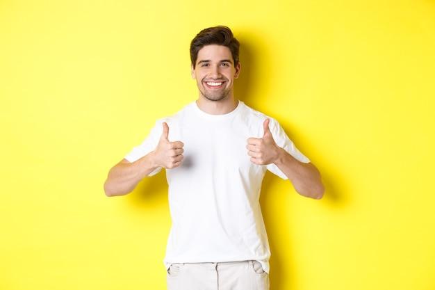 黄色の背景の上に立って、何かのように、または同意するように、承認で親指を立てて示す幸せな男の肖像画。