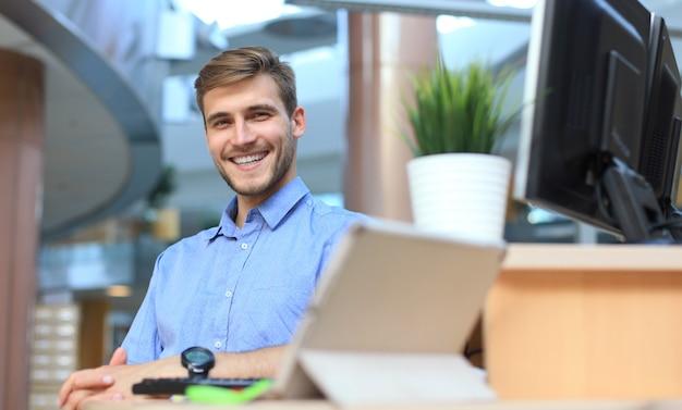 Портрет счастливого человека, сидящего за офисным столом, глядя на камеру, улыбаясь.