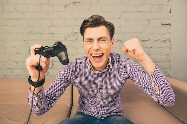 Портрет счастливого человека, выигрывающего видеоигру, держащего джойстик