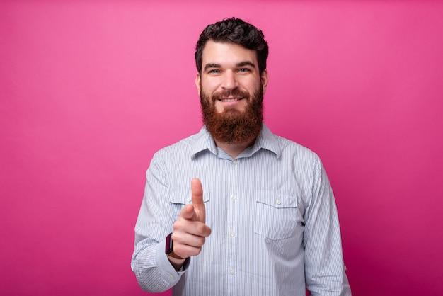 분홍색 배경 위에 서 있는 동안 캐주얼하게 카메라를 가리키는 수염을 기른 행복한 남자의 초상화