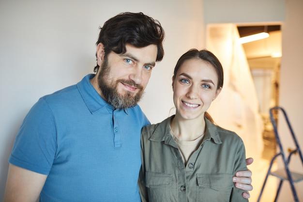 Портрет счастливой супружеской пары, обнимающейся во время совместного ремонта дома, копией пространства